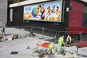 Workmen finish new pavement below a movie poster for the film Hop.