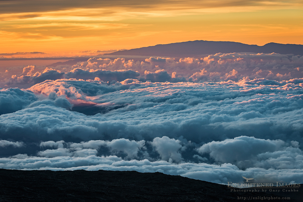 Looking out over a sea of clouds at sunset from the summit of Mauna Kea (13,800') toward Haleakala ( on the island of Maui), Big Island of Hawai'i, Hawaii