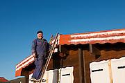 John Muir Way Older man panting beach hut, up a ladder, smiling