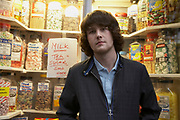 Young man standing in front of candy shop window with hands in pocket.