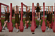 Female recruits in the first phase of their training perform assisted pull-ups as they rotate between different fitness stations.  Marine Corps Recruit Depot at Parris Island in South Carolina is where all male recruits living east of the Mississippi River and all female recruits from all over the US receive their arduous twelve week training in their quest to become marines. Even though there are two current active wars and a weak economy, recruitment has not been effected.  Actually, recruiting numbers have increased, with more young men and women looking toward the military for answers.