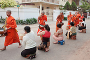 """Mar. 11, 2009 -- VIENTIANE, LAOS:  Buddhist Monks in Vientiane, Laos, go about their """"Tak Bat"""" or monks morning rounds. The monks collect alms in the form of food from people who line their route. Photo by Jack Kurtz / ZUMA Press"""