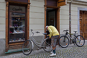 A cyclist locks up his bike on Trubarjeva Cesta (street) in the Slovenian capital, Ljubljana, on 28th June 2018, in Ljubljana, Slovenia. Ljubljana is a small city with flat terrain and a good cycling infrastructure. It was featured at eighth on the 'Copenhagenize' index listing the most bike-friendly cities in the world though bike theft is prevalent.