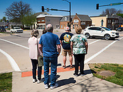 """03 MAY 2020 - PELLA, IOWA: People wait to cross Washington Street, the main street in downtown Pella, Iowa. Pella is a small community in central Iowa. The town's economy is driven by tourism and the Tulip Festival, the largest tourist event of the year, has already by canceled for 2020 because of fears that the festival could become a COVID-19 (Coronavirus/SARS-CoV-2) """"Super Spreader"""". The Governor of Iowa reopened 77 of Iowa's 99 counties. The counties that were reopened have reported low incidences of Coronavirus. Marion County, where Pella is located, has reported 12 cases of Coronavirus. There have been 9,169 confirmed cases of Coronavirus in Iowa, including 1,476 cases in the Des Moines area, less than one hour away. Many people from Des Moines drove to Pella this weekend to see the tulips for which the town is famous.     PHOTO BY JACK KURTZ"""
