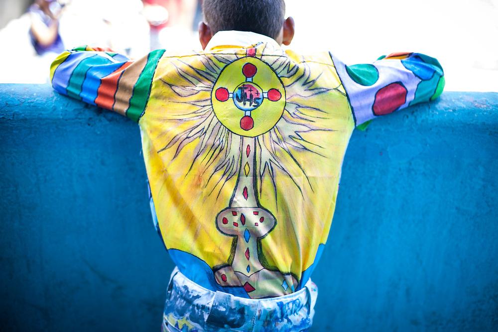 Detalle del atuendo de un participante de la festividad del Corpus Christi, representada en Venezuela a traves del ritual magico-religioso de los Diablos Danzantes. Los Diablos de Naiguata se identifican por pintar sus propios trajes y decorarlos con cruces, rayas y circulos, figuras que impiden que el maligno los domine. Las mascaras son en su gran mayoria animales marinos. Llevan escapularios cruzados, crucifijos y cruces de palma bendita. Naiguata, 30 Mayo 2013. (ivan gonzalez)