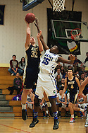 Essex's Aidan Travers (32) leaps over Colchester's Shane Grant (25) to take a shot during the boys basketball game between the Essex Hornets and the Colchester Lakers at Colchester High School on Tuesday night December 15, 2015 in Colchester. (BRIAN JENKINS/for the FREE PRESS)