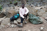 A porter rests at Barranco camp after a day of carrying supplies. Up to seven porters can support one singular hiker.