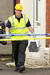 © Licensed to London News Pictures. 27/06/2012. Oldham , UK . A large explosion , believed to be caused by gas , has brought down at least one house in an Oldham terrace . Felix the cat is rescued from 4 Gordon Street by a member of fire services crew to the delight of his owners . Photo credit : Joel Goodman/LNP