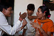 Deepak works with 16-year-old Hansa who is deaf and blind. They are learning tactile sign language. Hansa's brother is watching in the background. Deepak is trained by Sense International in Ahmadabad, India. Hansa is also supported by the Dhanki Community Project to lead a more independent life.