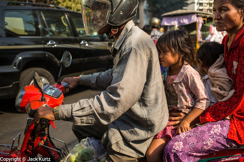 30 JANUARY 2013 - PHNOM PENH, CAMBODIA:  A family on a motorcycle navigates through traffic in Phnom Penh, Cambodia. Motorcycles are used as family transportation in most of Southeast Asia.    PHOTO BY JACK KURTZ