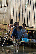 Mekong Delta. Young mother with child washing dishes in the river.