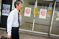 Local businessman passes by signs from a local advertising campaign saying 'We Love Toyota', in Toyota city, Japan, on Tuesday 21st April 2009.  In the first 3 months of 2009 the numbers of people seeking work at the local Toyota city 'Hello Work' employment office rose 133% compared to the first quarter of 2008. This increase is due to the jobs lost in the industries and companies which serve and supply the Toyota car company and automobile industry, for which Toyota city is famous.