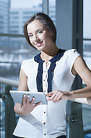 Businesswoman holding tablet device and smiling