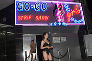Israel, Tel Aviv, two erotic dancers standing on the street outside the night club under the sign to tempt people into the club