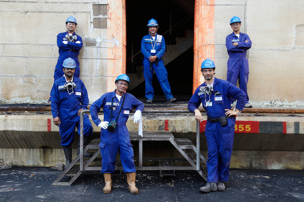 five male workers out in a ship yard