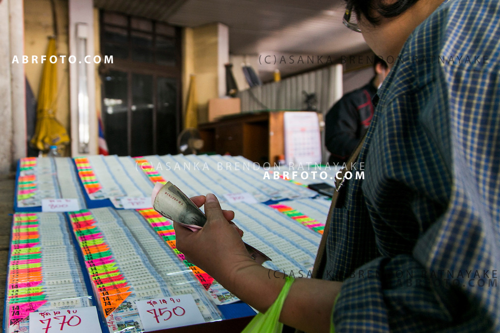 Street-side vendors unload discounted lottery tickets from the nearby Government Lottery Office. Over 92 million tickets are sold every month to Thais looking to collect a 3 million baht grand prize.