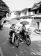 Girls carrying umbrellas while on motorcycles.