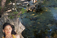 Portrait of teenage girl (16-17 years) relaxing on tree trunk by stream
