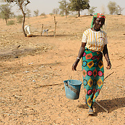 Mariama Maikoudil, approximately 20, returns from taking a bucket of water to her family's single sheep in the village of Kouka Samou in the Zinder region of Niger.