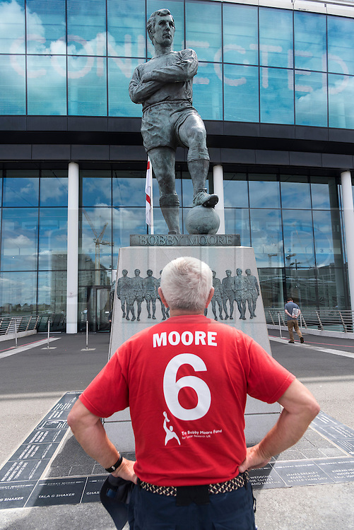 © Licensed to London News Pictures. 30/07/2016. A football fan views the bronze statue of England footballer BOBBY MOORE outside Wembley Stadium on the 50th anniversary of England beating Germany in the World Cup finals on 30th July 1966.  London, UK. Photo credit: Ray Tang/LNP