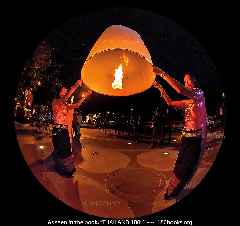 Women in traditional Thai clothes launch a Yi Peng lantern.