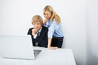 Businesspeople using laptop together at desk in office