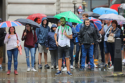 © Licensed to London News Pictures. 23/08/2018. London, UK. People shelter from the rain beneath umbrellas at Piccadilly Circus as wet weather returns to central London. Photo credit: Rob Pinney/LNP