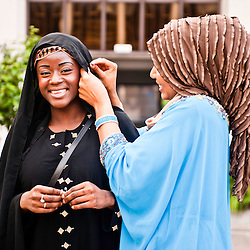 London, UK - 21 July 2012: Kay, Team GB Olympic discus thrower Abdul Buhari's wife, adjust the veil to a young woman before posing for pictures at the Ramadan Iftar 2012 celebrations hosted at the Islamic Cultural Centre (ICC) in Regents Park.