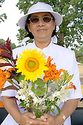 Asian woman holds beautiful bouquet orange tiger lilies and a sunflower. Dragon Festival Lake Phalen Park St Paul Minnesota USA