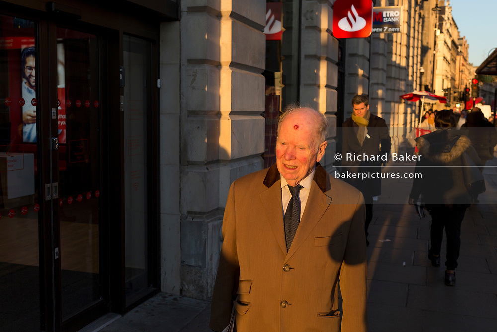 An elderly gentleman with a head blemish walks into winter sunshine, passing a branch of Santander on Piccadilly, on 20th January 2020, in London, England.