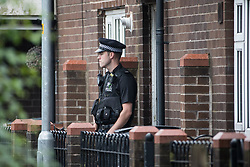 © Licensed to London News Pictures . 26/07/2017 . Oldham , UK . Police officer guarding front entrance of the house at the scene of an armed siege that began at 3.15am on Tuesday 25th July in a house on Pemberton Way in Shaw . A man named locally as Marc Schofield is reported to be holding a woman hostage after earlier releasing two children . The gas supply in the area has been cut off and several neighbouring properties have been evacuated . Photo credit : Joel Goodman/LNP