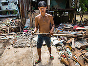 09 SEPTEMBER 2016 - BANGKOK, THAILAND:  A man walks past a partially demolished home in the Pom Mahakan Fort, one of 15 homes torn down by Bangkok officials over the weekend. Forty-four families still live in the Pom Mahakan Fort community. The city of Bangkok has given them provisional permission to stay, but city officials say the permission could be rescinded and the city go ahead with the evictions. The residents of the historic fort have barricaded most of the gates into the fort and are joined every day by community activists from around Bangkok who support their efforts to stay.           PHOTO BY JACK KURTZ
