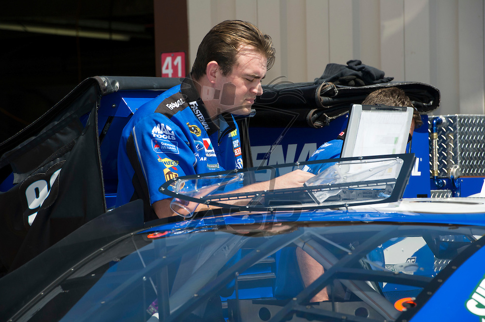 Brooklyn, MI - JUN 15, 2012: A crew member of the #99 race car checking the car's computer prior to practice runs for the Quicken Loans 400 race at the Michigan International Speedway in Brooklyn, MI.