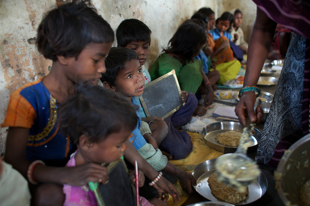 Children receive their midday meals in Mananbigha village Anganwadi (child care) centre. The Anganwadi centre has been running regularly for three months thanks to intervention of the local Nyadal: a local village court and justice system.<br /> <br /> Like much of rural Bihar state - particularly among low caste communities - the residents of Mananbigha regularly go hungry. Some have died as a result of food shortages. There is a scarcity of water in the area and no irrigation facility. Though there are schemes in place to support vulnerable families, it is an ongoing struggle for residents to claim benefits, including rations, that are by rights theirs. Oxfam partners have helped to promote awareness of social security schemes among residents in Mananbigha village and provided them the assistance to set up systems where they can get their views and complaints heard. The Nyadal, a local village court and justice system can refer serious problems or issues to the higher courts. The Nyadal also monitors the government PDS (Public Distribution System) and the Anganwadi (child care centre) midday meals scheme. The Mananbigha village vigilance committee reports to the Nyadal and a complain box allows residents to post concerns to the Nyadal. <br /> <br /> Photo: Tom Pietrasik<br /> Mananbigha village, Barachatti Block, Gaya District, Bihar. India<br /> February 25th 2011