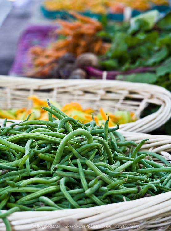 A large basket of fresh green beans at the farmers market.