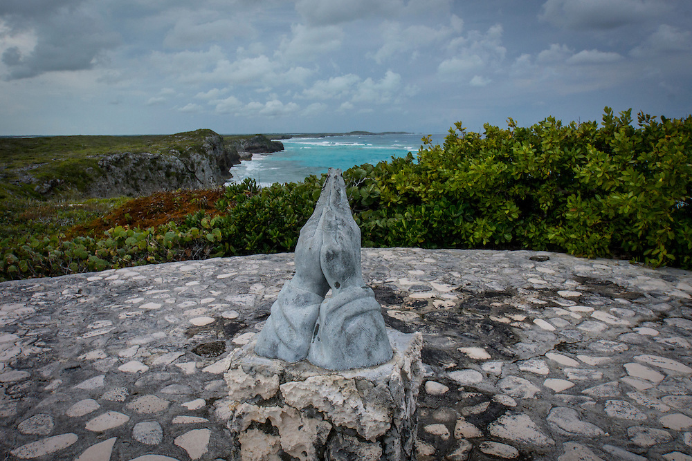 "The praying hands are at a stone lookout area called the ""Circle of Hope"".  The ""Circle of Hope"" is located at Mudjin Harbour on Middle Caicos island.  The praying hands are cast of bronze."