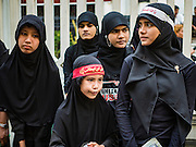 23 OCTOBER 2015 - YANGON, MYANMAR: Shia women wait for an Ashura procession to reach Mogul Mosque in Yangon. Ashura commemorates the death of Hussein ibn Ali, the grandson of the Prophet Muhammed, in the 7th century. Hussein ibn Ali is considered by Shia Muslims to be the third imam and the rightful successor of Muhammed. He was killed at the Battle of Karbala in 610 CE on the 10th day of Muharram, the first month of the Islamic calendar. According to Myanmar government statistics, only about 4% of the population is Muslim. Many Muslims have fled Myanmar in recent years because of violence directed against Burmese Muslims by Buddhist nationalists.    PHOTO BY JACK KURTZ