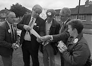 Austin Currie Canvas In Palmerstown (T1)..1989..07.06.1979..06.07.1989..7th June 1989..In the general election The Fine Gael Party chose Mr Austin Currie to contest for a seat in Dail Eireann. Well known as a civil rights activist and peace campaigner Mr Currie hoped to win a seat alongside running mate Mr Jim Mitchell.Mr Currie previously held a seat in the Northern Ireland Executive and held a position as Minister for Housing and Local Planning. Mr Currie is a founder member of the S.D.L.P...Image shows Mr Currie and his team planning the route that they would take in his quest to garner votes.