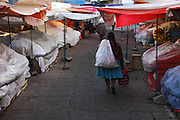 Woman walking through city market, Sucre, Bolivia