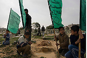 Palestinian children carry HAMAS flags as they recite prayers at the graves of friends and relatives January 16, 2009 at a cemetary in Rafah Gaza. The Israeli Defense Forces claim their sustained campaign has significantly degraded smuggling tunnels along  the corridor and the damaged the ability of HAMAS to smuggle weapons and cash into the Strip, but it has also killed civilians unlucky to have been still in the vicinity of targeted neighborhoods.
