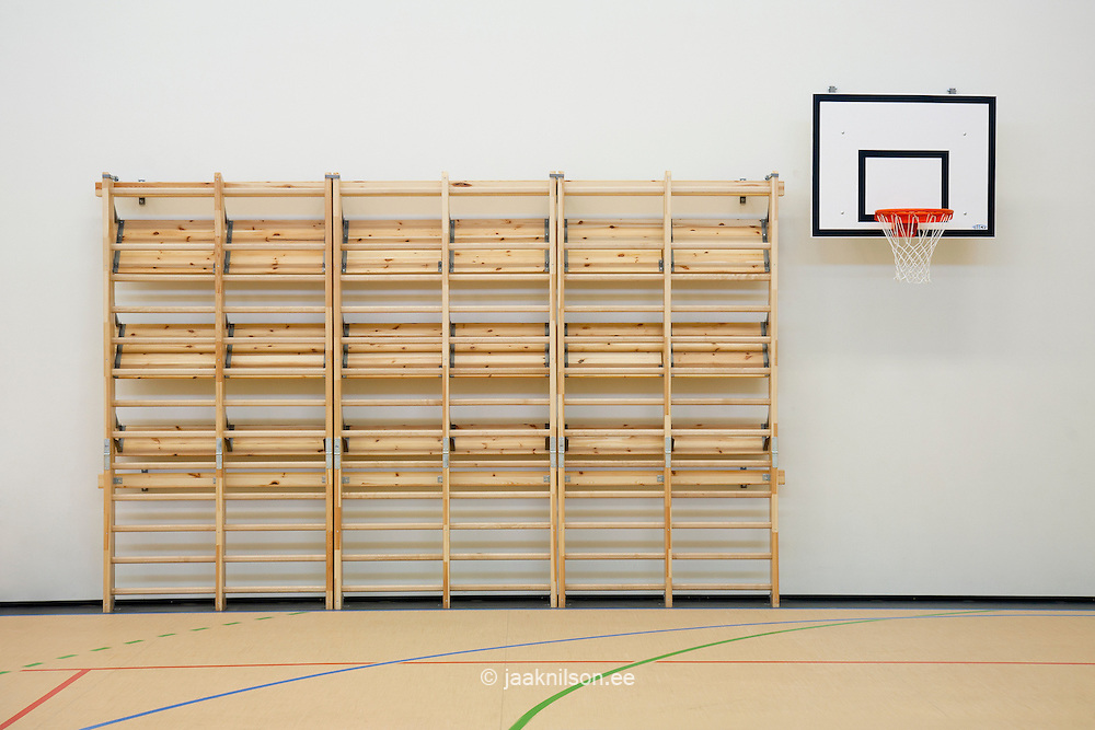 Indoor gym, basketball court with hoop and  backboard. Climbing equipment along wall. Village school in Metsapoole, Estonia.