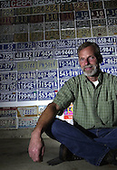 Tom Dzamko sits in front of one of the walls of his garage in Bethel, all of which are covered with license plates.  he has every make from ct as well as a plate from every state in the year 1999