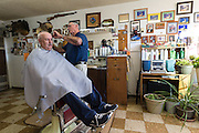 Nelson Cue, owner of Nelson's Barber Shop in Crescent, cuts the hair of John Tice of Crescent.