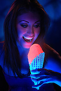 A young girl opens her mouth to take a bite out of a glowing cream cone.Black light
