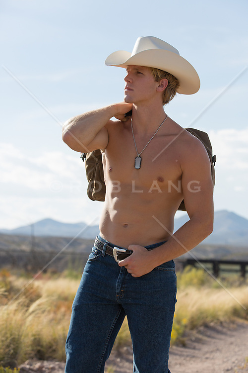 shirtless cowboy on a dirt road with a duffle bag