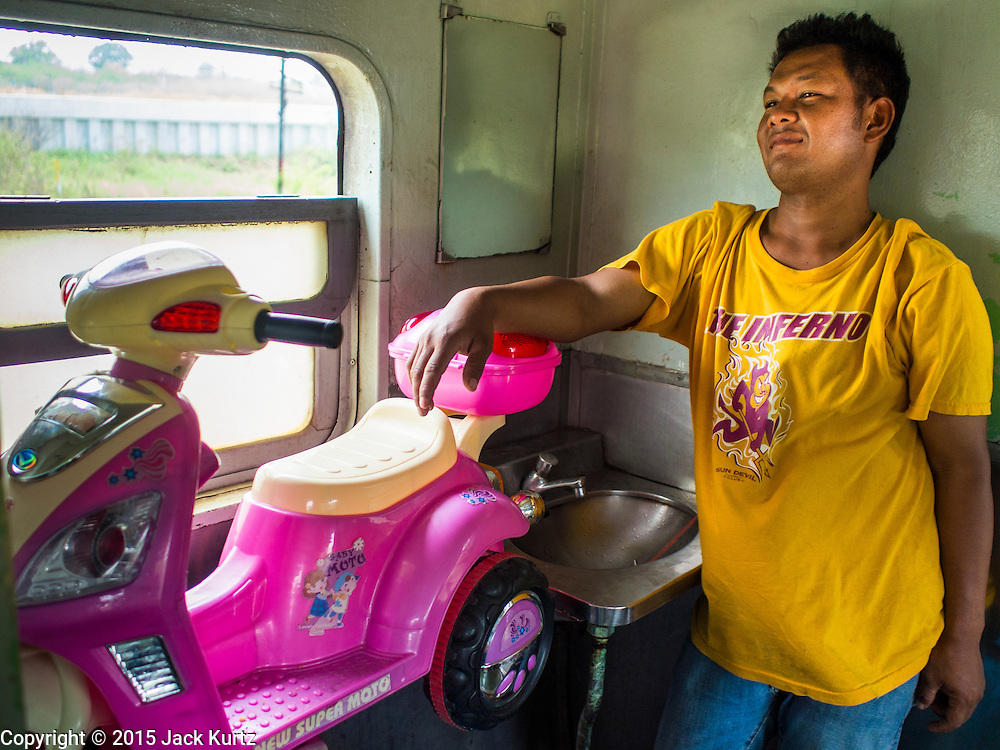 19 MARCH 2015 - AYUTTHAYA, AYUTTHAYA, THAILAND:  A passenger wearing an old Arizona State University tee shirt on the Ayutthaya to Bangkok third class train. The train line from Bangkok to Ayutthaya was the first rail built in Thailand and was opened in 1892. The State Railways of Thailand (SRT), established in 1890, operates 4,043 kilometers of meter gauge track that reaches most parts of Thailand. Much of the track and many of the trains are poorly maintained and trains frequently run late. Accidents and mishaps are also commonplace. Successive governments, including the current military government, have promised to upgrade rail services. The military government has signed contracts with China to upgrade rail lines and bring high speed rail to Thailand. Japan has also expressed an interest in working on the Thai train system. Third class train travel is very inexpensive. Many lines are free for Thai citizens and even lines that aren't free are only a few Baht. Many third class tickets are under the equivalent of a dollar. Third class cars are not air-conditioned.   PHOTO BY JACK KURTZ