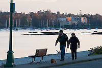 People enjoy the last of the sun during a stroll along Willows Beach, Oak Bay, Victoria, BC, Canada