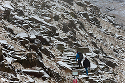 © Licensed to London News Pictures. 22/01/2019. Snowdonia, Gwynedd, Wales, UK.  Two hikers sets off to climb Mount Snowden as snow showers continue in Snowdonia National Park, Gwynedd, UK. credit: Graham M. Lawrence/LNP