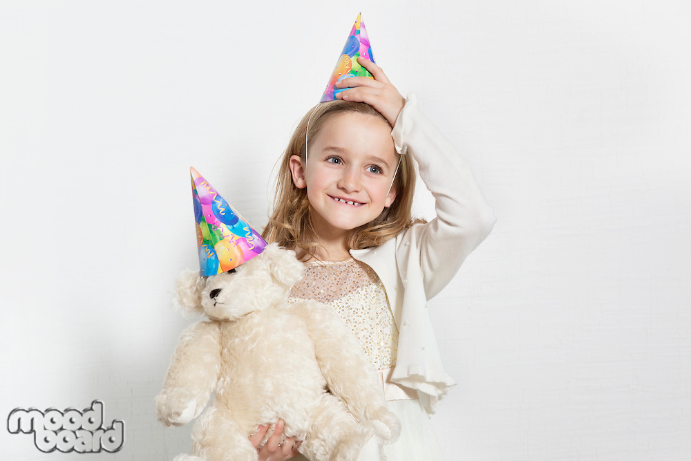 Happy young birthday girl wearing party hat with teddy bear over colored background