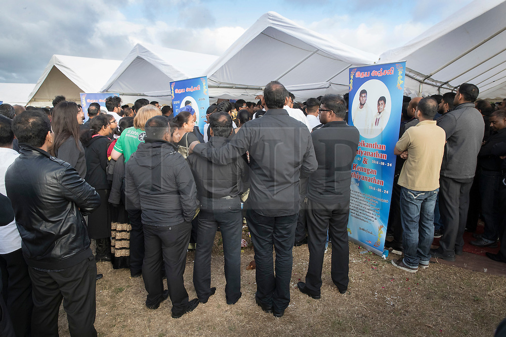 © Licensed to London News Pictures. 04/09/2016. London, UK. Relatives and friends pay respect in a tent holding the coffins of brothers Kenigan and Kobi Nathan at a joint funeral held at Winn's Common Park for five men who drowned at Camber Sands last month.  The five men: Kurushanth Srithavarajah, brothers  Kenigan and Kobi Nathan, Inthushan Sri and Nitharsan Ravi were all friends from London.  They got into difficulty in the sea of Camber Sands on August 24. Photo credit: Peter Macdiarmid/LNP